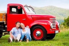 Pares superiores que sentam-se no carro vermelho do vintage imagem de stock