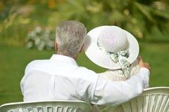 Pares superiores que sentam-se no jardim tropico do hotel imagens de stock