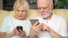Pares superiores que sentam-se no sofá em casa Utilização moderna dos pensionista móvel, consultando, lendo a notícia filme