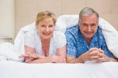 Pares superiores que sorriem sob a edredão Imagens de Stock Royalty Free