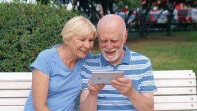 Pares superiores que têm o grande tempo que senta-se no banco no relaxamento de conversa do parque, consultando no smartphone video estoque
