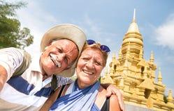 Pares superiores que tomam o selfie no templo dourado em Ko Samui - pessoa aposentado feliz que viaja às maravilhas de Tailândia  fotografia de stock