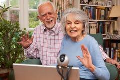 Pares superiores usando o portátil e a câmara web para falar à família Fotos de Stock Royalty Free