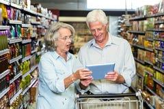 Pares superiores usando a tabuleta no supermercado Imagens de Stock Royalty Free