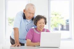 Pares superiores usando um portátil em casa imagem de stock