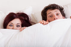 Pares surpreendidos na cama Fotografia de Stock Royalty Free