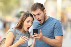 Pares surpreendidos que olham na linha meio em um telefone Foto de Stock Royalty Free