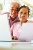 Pares taiwaneses mayores que trabajan en el ordenador portátil Fotografía de archivo libre de regalías