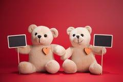 Pares Teddy Bears en fondo rojo Tarjeta del día de tarjetas del día de San Valentín Corazones rojos imagenes de archivo