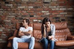 Pares trastornados frustrados después de la pelea que se sienta en el sofá en casa Fotografía de archivo libre de regalías