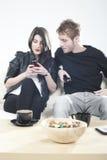 Pares trastornados que miran a los teléfonos móviles Imagenes de archivo