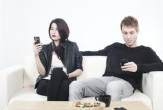 Pares trastornados que miran a los teléfonos móviles Fotos de archivo libres de regalías