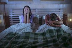 Pares tristes após a luta doméstica com o grito deprimido da mulher e o noivo frustrante que sentam-se na cama infeliz no esforço fotos de stock