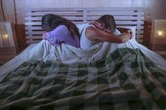 Pares tristes após a luta doméstica com o grito deprimido da mulher e o noivo frustrante que sentam-se na cama infeliz no esforço fotografia de stock