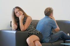 Pares tristes após o argumento ou dissolução que senta-se em um sofá na sala de visitas em uma casa interna imagens de stock