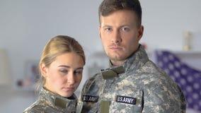 Pares tristes de los soldados americanos que miran el primer de la cámara, profesión peligrosa almacen de video