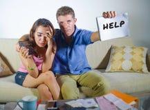 Pares tristes e preocupados atrativos novos que explicam junto no sofá do esforço financeiro em casa no problema doméstico da fin foto de stock royalty free