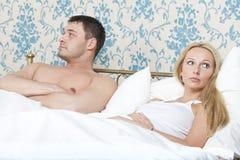 Pares tristes na cama Fotografia de Stock Royalty Free
