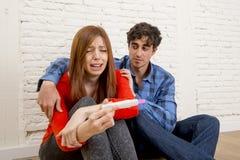Pares tristes novos assustado com o grito positivo cor-de-rosa de leitura do teste de gravidez da menina grávida oprimido Fotos de Stock Royalty Free