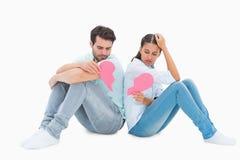 Pares tristes que sentam-se guardando duas metades de coração quebrado Fotografia de Stock Royalty Free