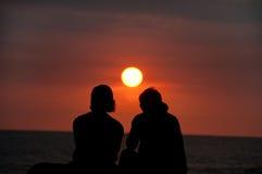 Pares tropicais das férias no por do sol de observação da praia Fotos de Stock Royalty Free