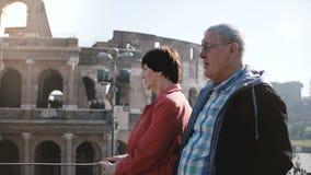 Pares turísticos caucásicos mayores activos felices que disfrutan de la vista del coliseo famoso junto durante viaje a Roma, Ital almacen de metraje de vídeo