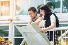 Pares turísticos con el mapa que busca una manera en la ciudad Imagenes de archivo