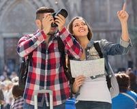Pares turísticos con la cámara en la ciudad Imágenes de archivo libres de regalías