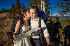 Pares turísticos de la boda que se besan con el mapa en manos Luna de miel en las montañas Imágenes de archivo libres de regalías