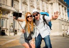 Pares turísticos de los amigos hermosos que visitan España en el intercambio de los estudiantes de los días de fiesta que toma la fotografía de archivo