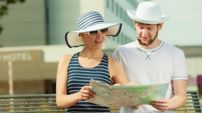 Pares turísticos en la ciudad que mira para arriba direcciones en mapa Fotografía de archivo