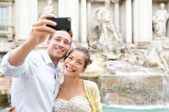 Pares turísticos en viaje en Roma por la fuente del Trevi Imagen de archivo