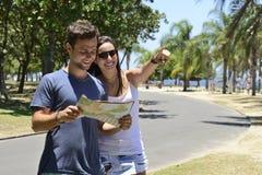 Pares turísticos felices con el mapa Imagen de archivo libre de regalías