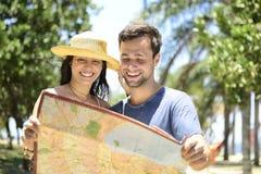 Pares turísticos felices con el mapa Imagen de archivo