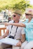 Pares turísticos felices que miran el mapa en la ciudad Fotos de archivo libres de regalías