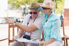 Pares turísticos felices que miran el mapa en la ciudad Imágenes de archivo libres de regalías