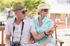 Pares turísticos felices que miran el mapa en la ciudad Fotografía de archivo
