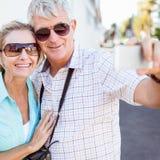 Pares turísticos felices que toman un selfie en la ciudad Foto de archivo