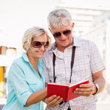 Pares turísticos felices usando la guía turística del viaje en la ciudad Fotos de archivo