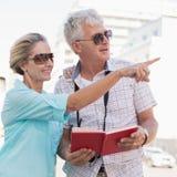 Pares turísticos felices usando la guía turística del viaje en la ciudad Fotos de archivo libres de regalías