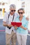 Pares turísticos felices usando la guía turística del viaje en la ciudad Foto de archivo