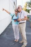 Pares turísticos felices usando la tableta en la ciudad Imágenes de archivo libres de regalías