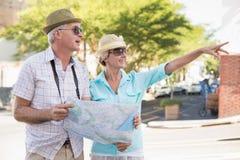 Pares turísticos felices usando mapa en la ciudad Foto de archivo libre de regalías