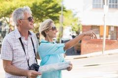 Pares turísticos felices usando mapa en la ciudad Fotografía de archivo libre de regalías
