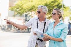 Pares turísticos felices usando mapa en la ciudad Fotos de archivo libres de regalías