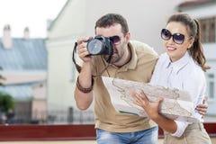 Pares turísticos jovenes en la ciudad al aire libre que toma imágenes juntas Fotografía de archivo libre de regalías
