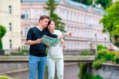 Pares turísticos jovenes que viajan el días de fiesta en Europa Familia caucásica con el mapa de la ciudad en busca de atraccione Imagen de archivo libre de regalías