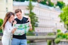 Pares turísticos jovenes que viajan el días de fiesta en Europa Familia caucásica con el mapa de la ciudad en busca de atraccione Fotos de archivo libres de regalías