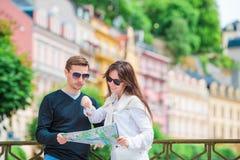 Pares turísticos jovenes que viajan el días de fiesta en la sonrisa de Europa feliz Familia caucásica con el mapa de la ciudad en Fotos de archivo libres de regalías