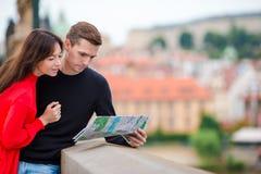 Pares turísticos jovenes que viajan el días de fiesta en la sonrisa de Europa feliz Familia caucásica con el mapa de la ciudad en Fotografía de archivo libre de regalías